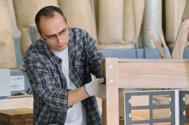 Produzione di mobili, ritratto maschio carpentiere in legno officina che fa sedia di legno. Foto Premium