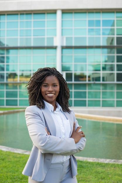 Professionista femminile sorridente allegro che posa vicino all'ufficio Foto Gratuite
