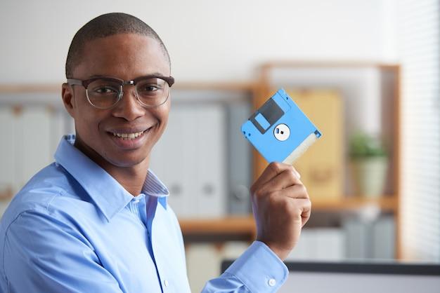 Professionista nero che tiene il floppy disk in ufficio Foto Gratuite
