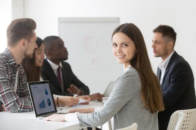 Professionista o stagista sorridente della donna di affari che esamina macchina fotografica la riunione Foto Gratuite