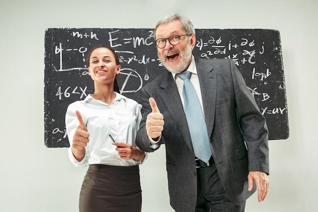 Professore maschio e giovane donna contro la lavagna in aula Foto Gratuite