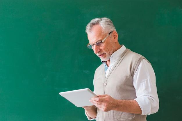 Professore maschio senior che per mezzo della compressa vicino alla lavagna Foto Gratuite