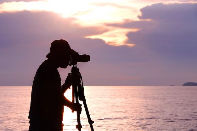 Profili il fotografo che prende la foto della luce del tramonto con il treppiede in mare in tailandia. il cielo ha una tonalità di colore viola e rosa. Foto Premium
