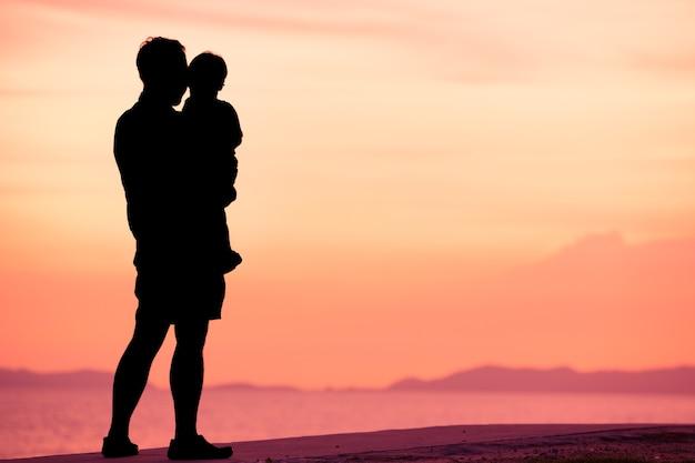 Profili il padre ed il figlio sulla spiaggia nel tempo del tramonto con il cielo crepuscolare Foto Premium