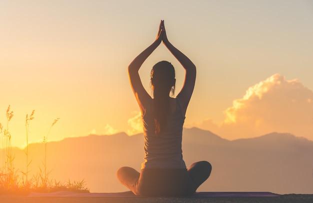Profili l'yoga di pratica della ragazza di forma fisica sulla montagna con la luce del sole Foto Premium