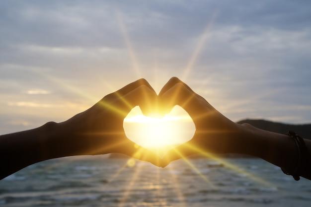 Profili la mano nella forma del cuore con alba sui precedenti della spiaggia Foto Premium