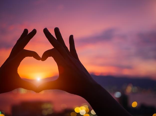 Profili la mano per essere una forma del cuore durante il fondo del tramonto. Foto Premium