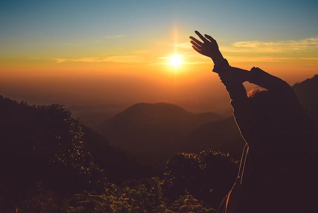 Profili le mani in aumento della donna sulla montagna nella mattina con luce d'annata, tailandia del nord Foto Premium