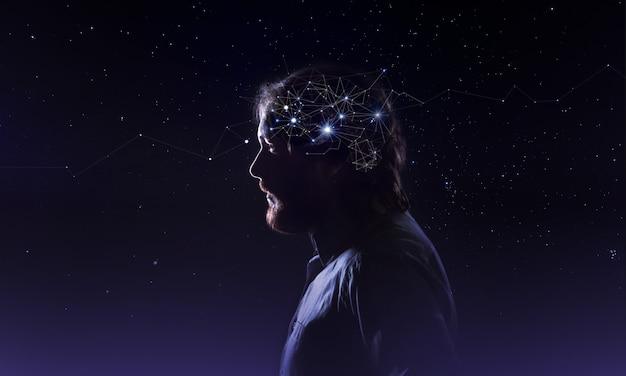 Profilo di una testa di uomo barbuto con neuroni simbolo nel cervello. pensando come le stelle, il cosmo dentro l'umano, lo sfondo del cielo notturno Foto Premium
