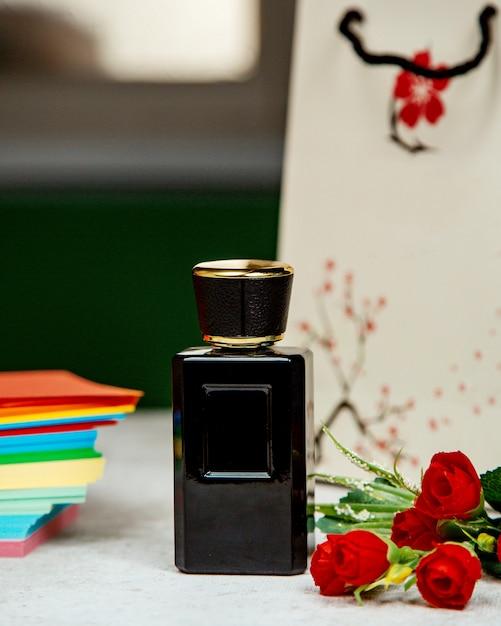 Profumo in bottiglia nera sul tavolo Foto Gratuite