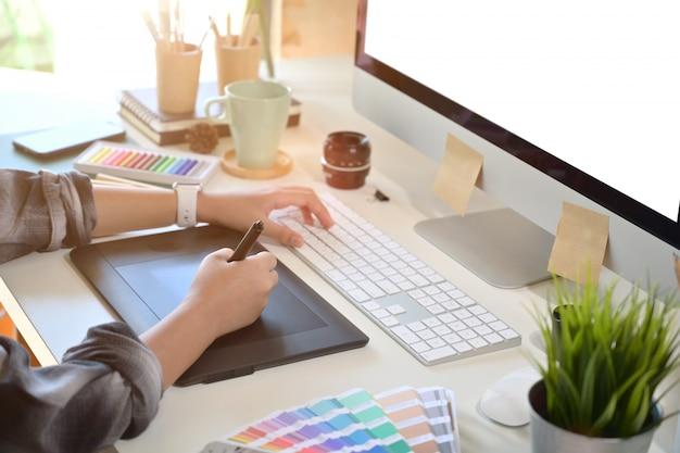 Progettista creativo che utilizza la tavoletta digitale del disegno nel posto di lavoro dello studio Foto Premium