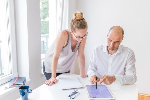 Progettista femminile che esamina uomo che mostra con lo stilo sulla compressa digitale grafica nel luogo di lavoro Foto Gratuite
