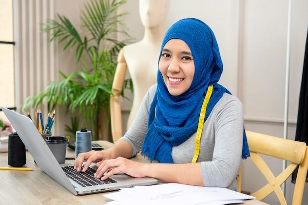 Progettista musulmano asiatico della donna che lavora nel suo negozio di sarto Foto Premium