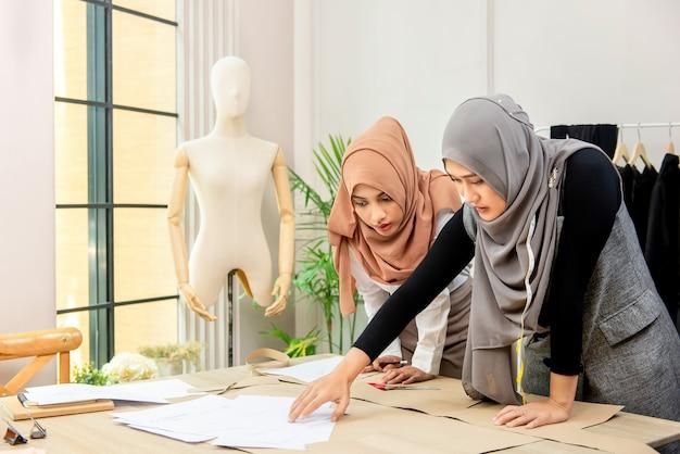 Progettista musulmano asiatico di fasion della donna che lavora con il collega Foto Premium