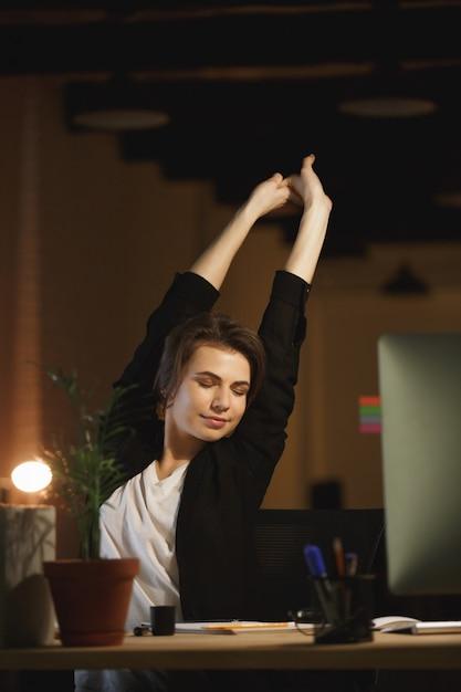 Progettista stanco della giovane donna che si siede nell'ufficio Foto Gratuite