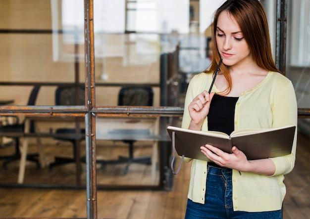 Programma di organizzazione della giovane bella donna in ufficio Foto Gratuite