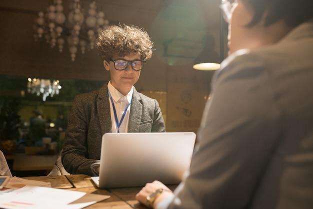 Programmatore astuto che utilizza computer portatile nell'ufficio scuro Foto Premium