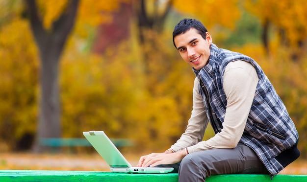 Programmatore con il taccuino che si siede nel parco di autunno Foto Premium