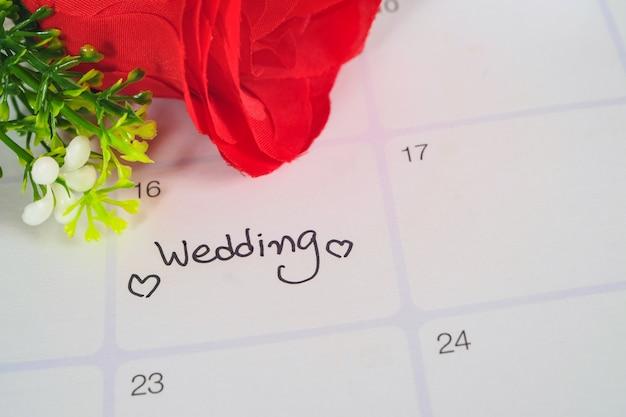 Promemoria giorno delle nozze nella pianificazione del calendario con la rosa rossa. Foto Premium