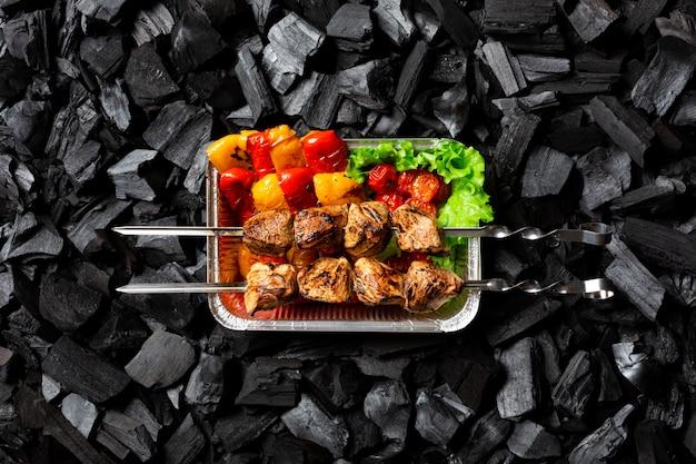 Pronto shish kebab. verdure grigliate e carne su spiedini in un contenitore monouso in alluminio. Foto Premium