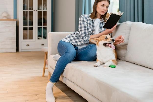 Proprietario della femmina e del cane che legge un libro sullo strato Foto Gratuite