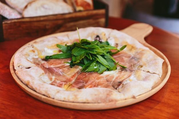 Prosciutto di parma topping di pizza con razzo sul piatto di legno arrotondato con pane a fette in scatola di legno in background. Foto Premium