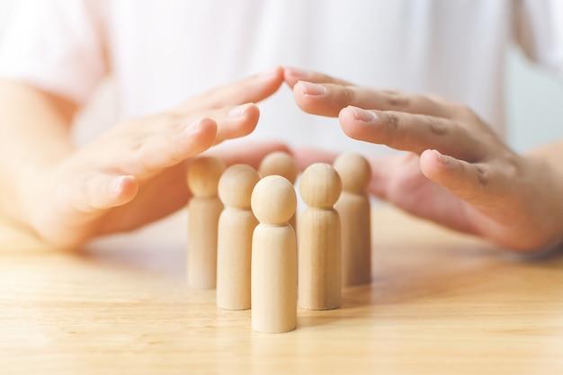 Protezione delle persone concetto di salute e assicurazione. la protezione della mano protegge l'essere umano di legno sulla tavola Foto Premium