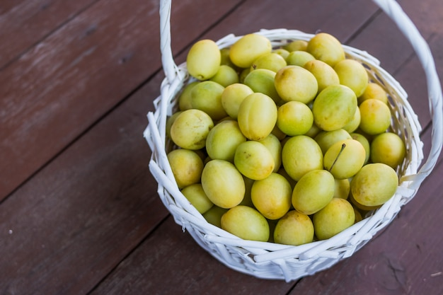 Prugne gialle e verdi variopinte succose mature in un canestro di vimini. Foto Premium