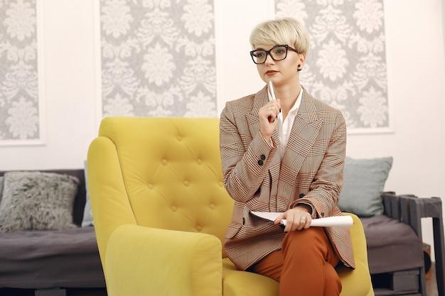 Psicologo con gli occhiali seduto su una sedia in ufficio Foto Gratuite