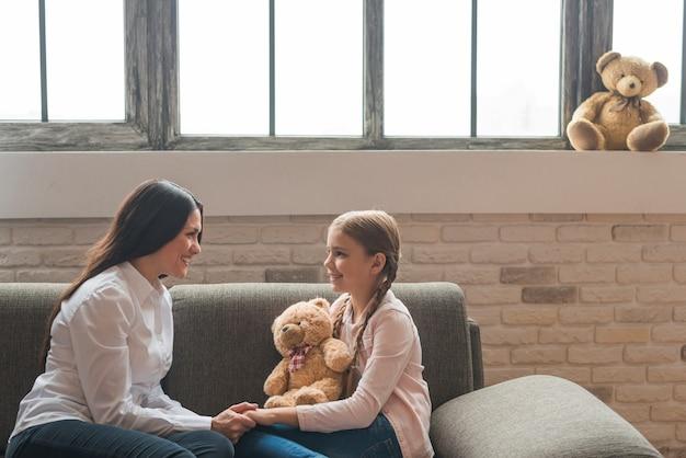 Psicologo femminile amichevole sorridente che parla con la ragazza che si siede sul sofà Foto Gratuite