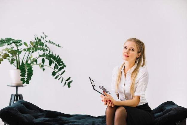 Psicologo femminile che si siede sul foglio della prova del inkblot della tenuta del rorschach dello strato sulla lavagna per appunti Foto Gratuite