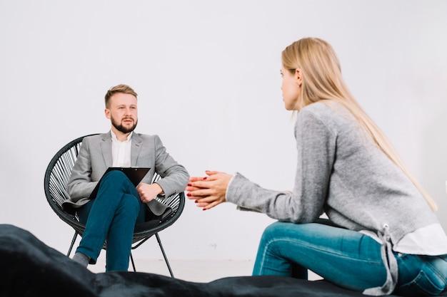 Psicologo maschio che parla con il suo giovane paziente femminile alla sessione di terapia Foto Gratuite