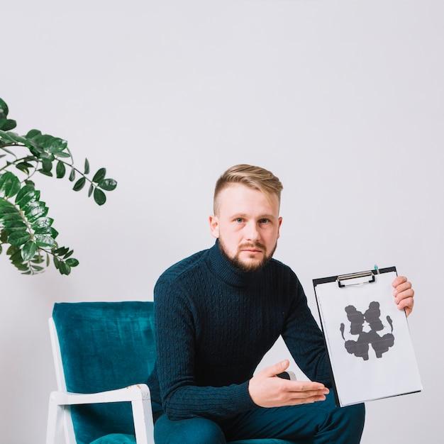Psicologo maschio che si siede sulla sedia del braccio che mostra la carta della prova del inkblot del rorschach Foto Gratuite