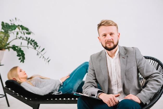 Psicologo maschio sicuro che si siede sulla sedia davanti al suo paziente femminile Foto Gratuite
