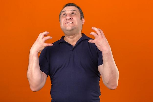 Pugni di serraggio da portare della camicia di polo dell'uomo invecchiato centrale che si arrabbiano sopra la parete arancione isolata Foto Gratuite