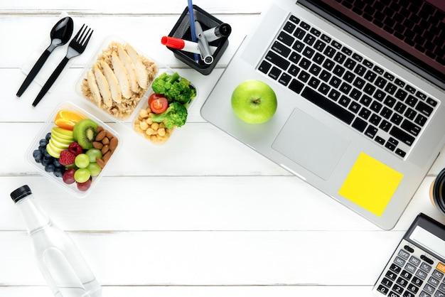 Pulisca il cibo a bassa percentuale di grassi sano con il computer portatile sul tavolo di lavoro Foto Premium