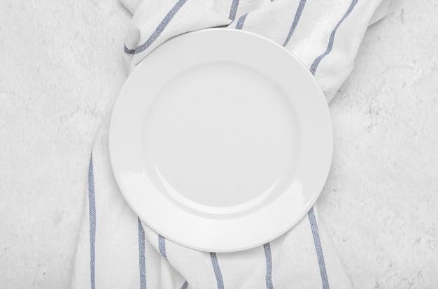 Pulisca il piatto bianco sull'asciugamano fresco con le bande su un fondo minimalista leggero di pietra. Foto Premium