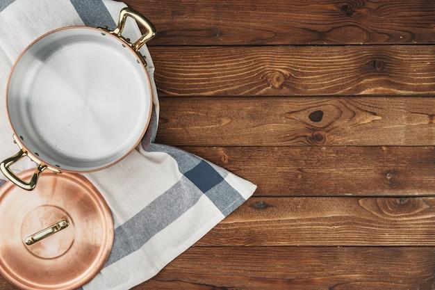 Pulisca l'articolo da cucina di rame brillante sul bordo di legno Foto Premium