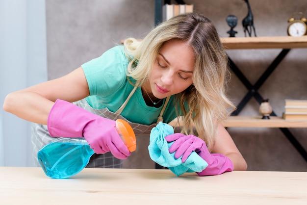 Pulitore femminile grazioso che pulisce scrittorio di legno con spruzzo detergente e panno Foto Gratuite