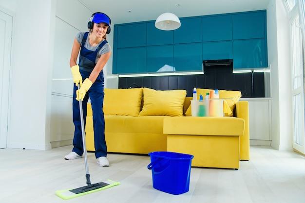 Pulitore professionale femminile giovane bella in uniforme speciale con le cuffie che lava il pavimento con la zazzera ed ascolta musica all'appartamento. Foto Premium