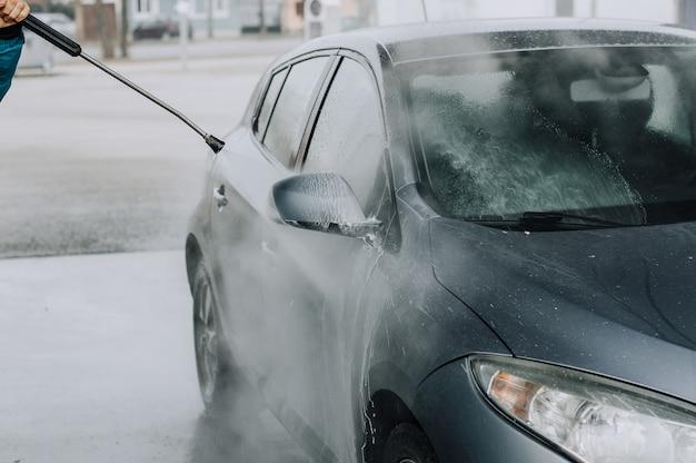 Pulizia dell'auto con acqua ad alta pressione. Foto Premium