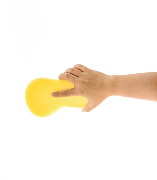 Pulizia della casa e dei servizi igienico-sanitari: mano che regge una spugna gialla bagnata con schiuma isolata su bianco Foto Premium