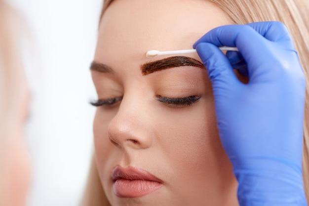 Pulizia della faccia del cliente durante il make-up permanente. Foto Premium