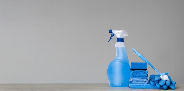 Pulizia flacone spray blu con dispenser in plastica, spugna, spazzola per strofinare, panno per polvere e guanti di gomma su grigio Foto Premium