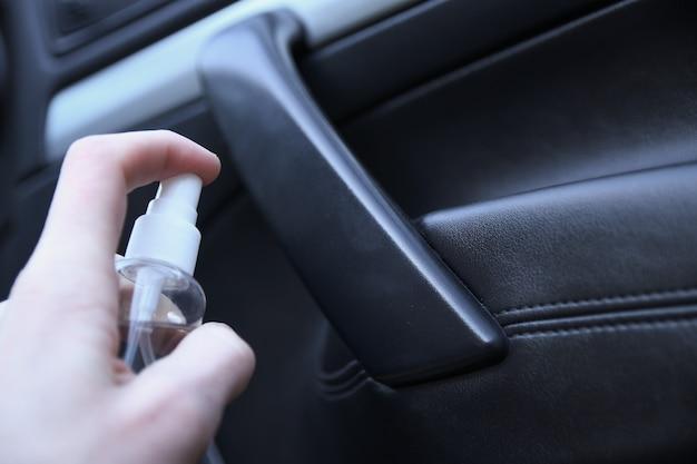 Pulizia interna dell'auto con liquido disinfettante. disinfezione del volante e delle maniglie dell'auto. coronavirus, protezione covid-19. veicolo disinfettante all'interno Foto Premium