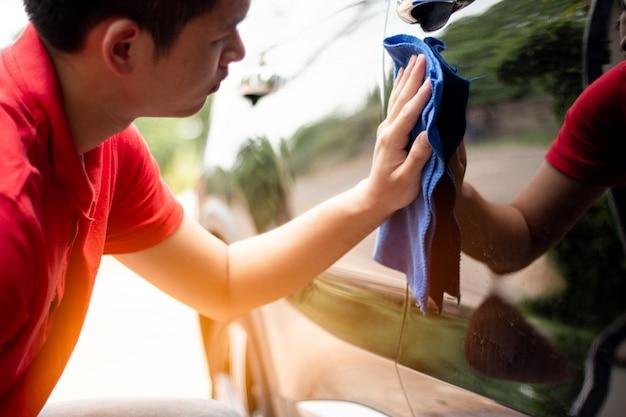 Pulizia utilizzare un asciugamano per auto per lavare la macchina Foto Premium