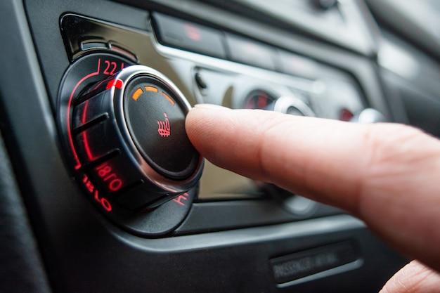 Pulsante per il riscaldamento del primo piano dei sedili dell'auto. la mano maschile preme il pulsante per riscaldare i sedili dell'auto. Foto Premium