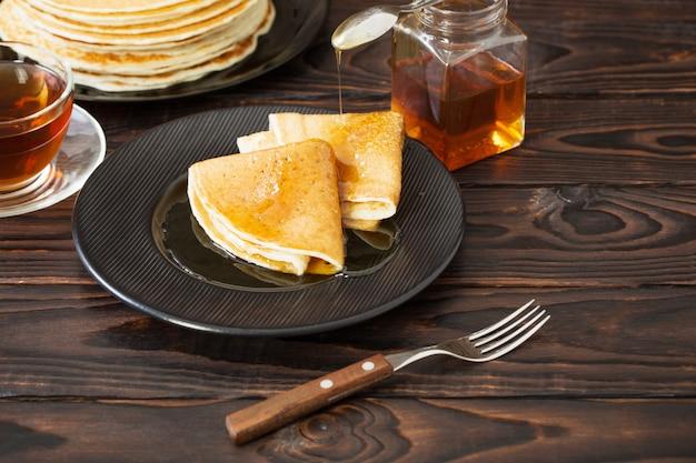 Puncakes con miele e la tazza di tè su fondo in legno vecchio Foto Premium