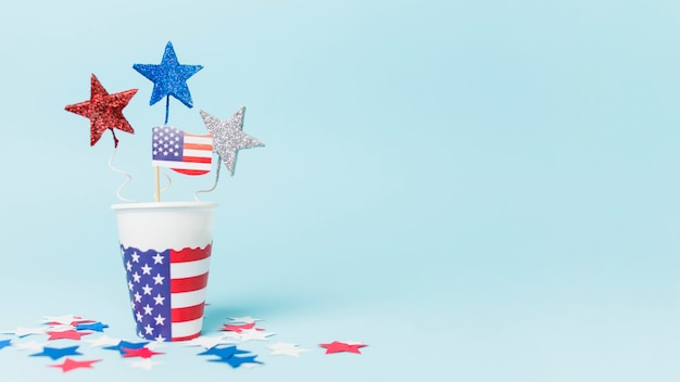 Puntelli della bandiera e della stella degli sua nella tazza eliminabile contro fondo blu Foto Gratuite