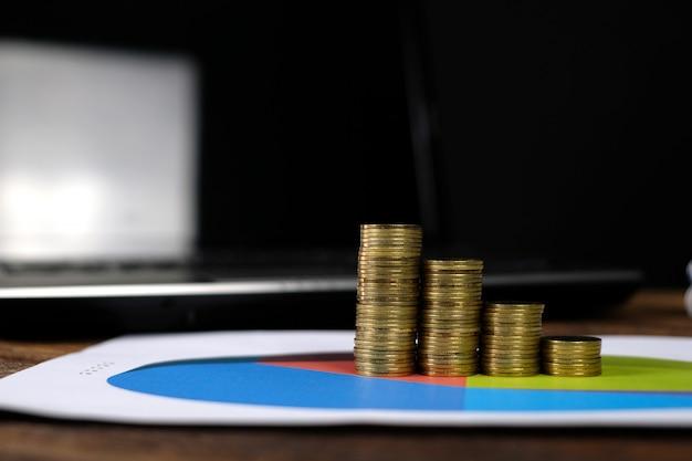 Punto delle pile delle monete con il computer portatile del taccuino e il grafico finanziario Foto Premium